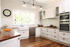 biała kuchnia z drewnianym blatem czarujący minimalizm