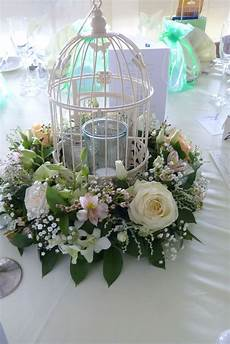 birdcage centrepiece filled with candles glassware and surrounded by a circlet of fresh