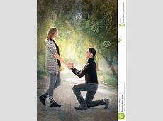 Kneeling Man Proposing With An Engagement Ring Stock Image