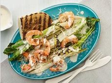 classic greek salad topped with grilled calamari skewers_image