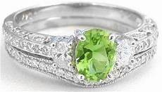 vintage inspired peridot and oval diamond engagement ring and wedding band in 14k white gold gr
