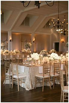 gold ivory and white wedding reception decor with white florals in glass vessels place