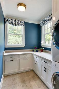 a blue and white laundry room is viewed with bold blue painted walls and white cabinetry blue