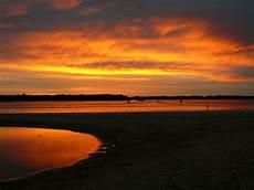 Gambar Orang Di Pantai Saat Matahari Terbenam