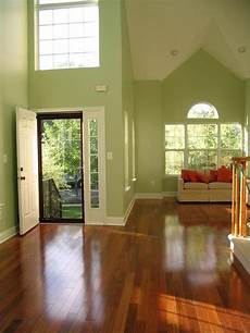 light green walls and high open ceilings balanced by cherry cherry floors