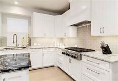contemporary white kitchen with gray glass backsplash