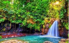 nature landscape waterfall with turquoise blue water rock tropical green vegetation sun rays