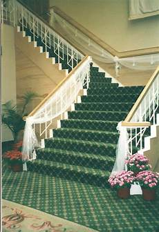 tulle swags with made bows grace this stair case leading guests to the reception in the
