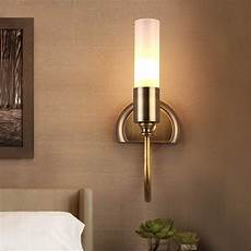 rustic cylinder glass shade 1 light indoor wall sconce with curved arm in brass indoor sconces
