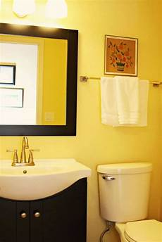 small yellow bathroom with framed black mirror and vanity