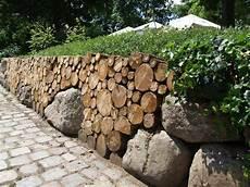 interessante gartenmauer aus holz und massisven steinen