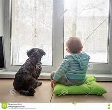 Baby Mit Dem Hund Der Durch Ein Fenster Im Winter Schaut