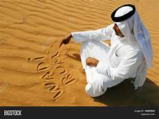 un following tradition to un traditional arabic man writing sand image photo bigstock