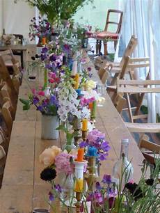 coloured candles and flowers in vintage mismatched vessels
