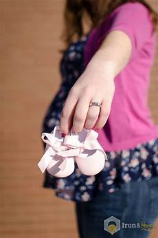 mom holding baby shoes showing wedding ring with baby bump in the background