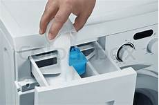 pours detergent into the washing machine stock photo