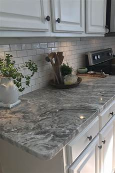 brown granite with small white subway tiles and