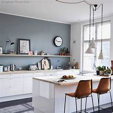 grey wall with white cabinets and warm brown chairs crisp and clean kitchen inspiration