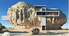an innovative house carved out of a house inside a rock shows concrete slabs contrasting