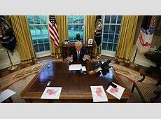 pictures behind trumps desk