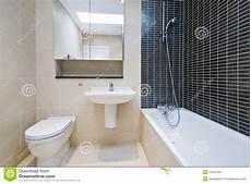 modern en suite bathroom in beige with black tiles stock