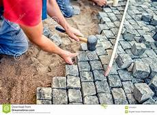 Paving With Granite Stones Workers Using Industrial