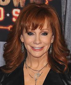 reba mcentire wavy dark copper hairstyle with layered bangs