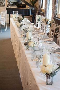 winter wedding ideas top table decoration small vases filled with white flowers and silvery