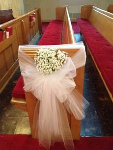 tulle bows with a touch of baby s breath on pews wedding