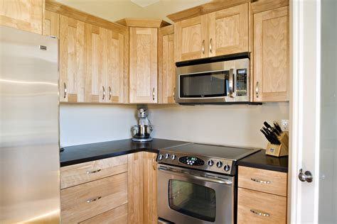 wooden birch cabinets with black counter tops to match
