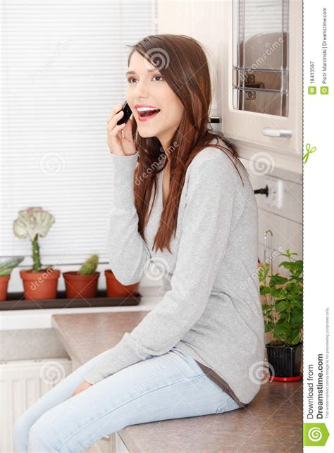 Talking Kitchen by Talking By Moibile Phone In Kitchen Stock Image