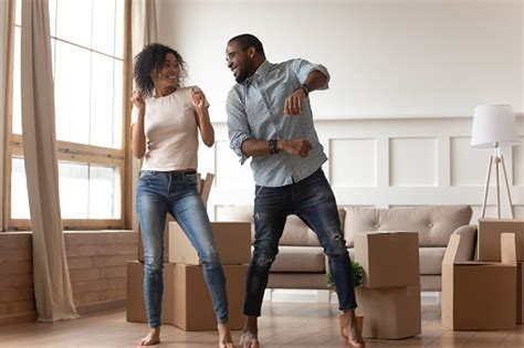 happy african couple dancing laughing  living room  boxes stock photo  image