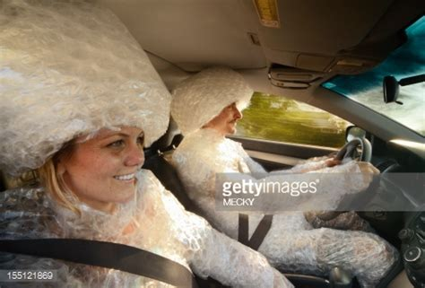 Couple Wrapped In Bubble Wrap Driving In Car Stock Photo