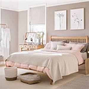 Pale pink bedroom with wooden furniture and woven