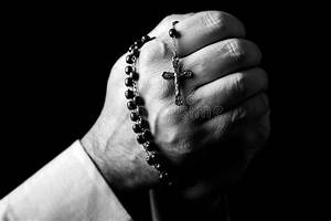 Male Hands Praying Holding A Rosary With Jesus Christ In ...