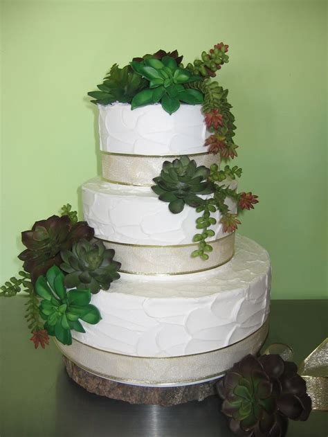 A Wedding Cake Decorated With Succulents Wedding Cakes
