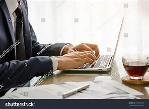 businessmans hand typing on computer keyboard stock photo With documents typing job