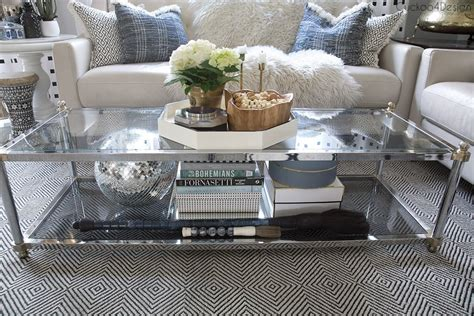 But instead of stacking them, consider splaying them out in a neat grid and layering the rest of your a clear coffee table lends this room a modern feel and puts both the rug and the storage baskets beneath it on display. How to style a two-tier coffee table | Cuckoo4Design