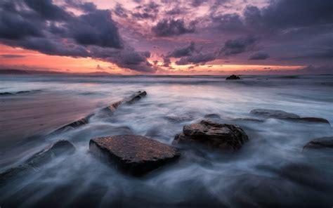 sea coast  rocks waves dark sky  clouds red