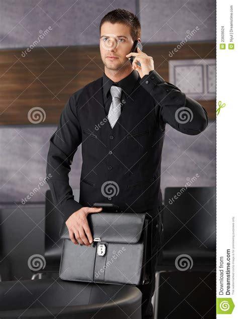 bureau des entr馥s homme d affaires bel dans l entrée de bureau avec le mobile