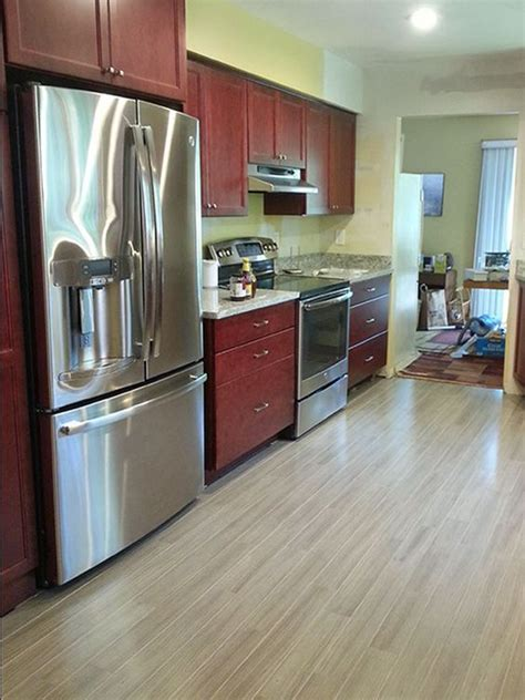 cherry cabinets with gray countertops grey hardwood floors accent a modern kitchen with cherry