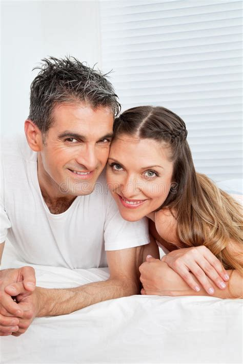 married couple cuddling  bed stock photo image