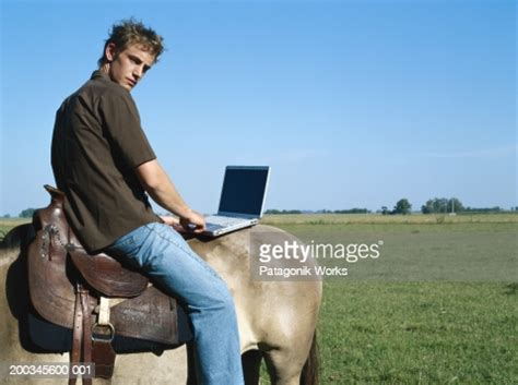 young man sitting   horse  laptop side