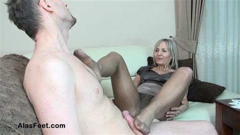 Blonde Milf In Black Pantyhose Is Giving A Footjob To Her
