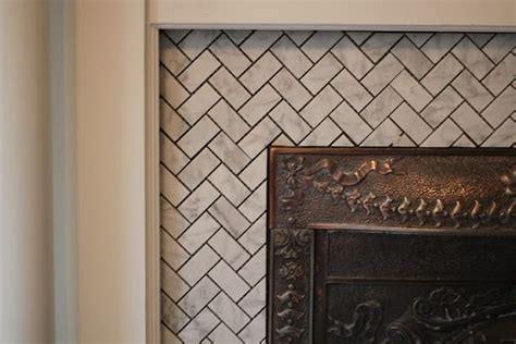 herringbone tile fireplace surround with white grout