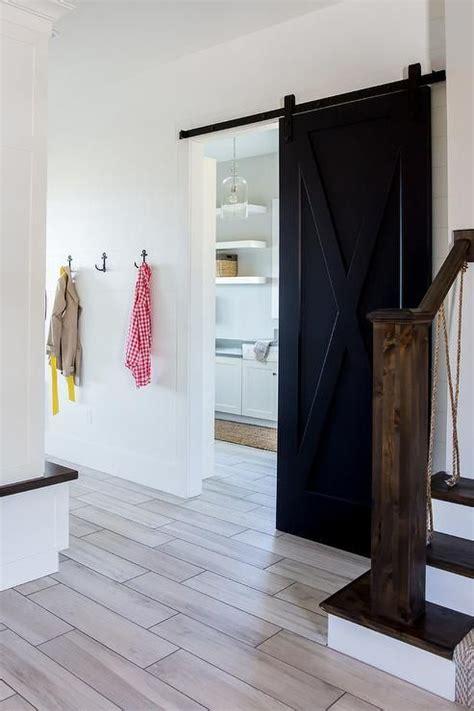 wood  floor tiles lead   black barn door  rails
