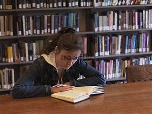 Young woman reading a book in the library - Download People