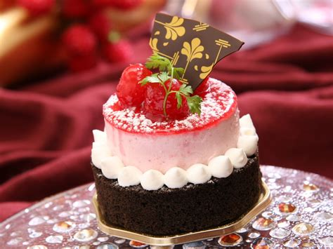chocolate cake with white icing and strawberry on top with