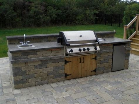 An Outdoor Kitchen With Napoleon Grill, Sink, And Fridge