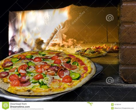 pizza coming    wood burning pizza oven stock image